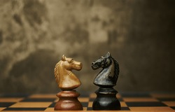 Wooden chess pieces knights facing each other on a vintage chessboard. Confrontation and rivalry concept, selective focus.
