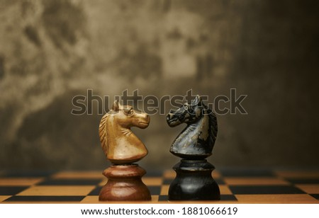 Wooden chess pieces knights facing each other on a vintage chessboard. Confrontation and rivalry concept, selective focus. Foto stock ©