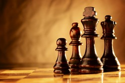Wooden chess pieces standing in a line on a chessboard in dramatic sepia toned lighting with copyspace