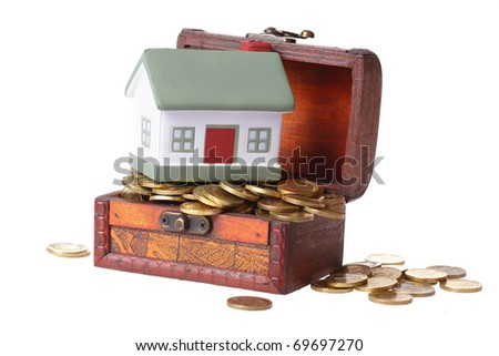 Wooden chest with coins and a small house. The concept of accumulation of money for habitation purchase