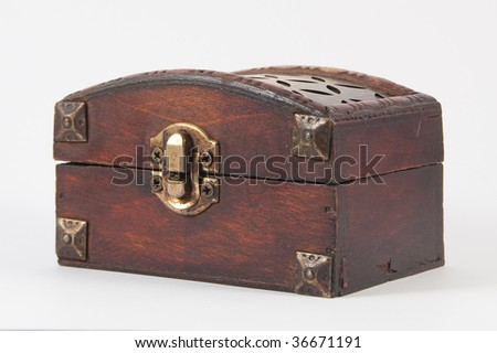 Wooden chest with metal lock and some carvings at the top. - stock photo