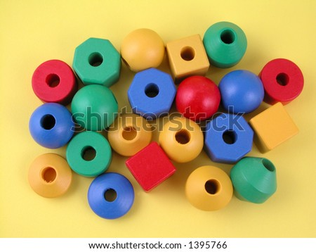 wooden childrens blocks of different colors yellow background stock
