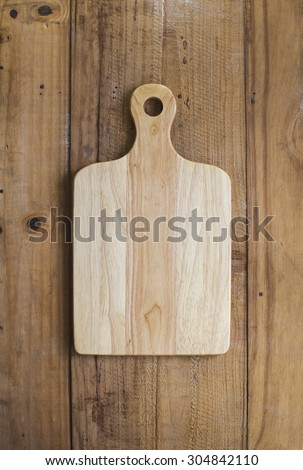 Wooden chop board on rustic wooden table top. Top view.