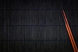 wooden chopsticks on the black bamboo mat background