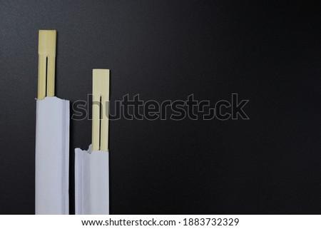 Wooden chopsticks, sushi sticks sealed in paper on a black background Foto stock ©