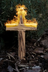 wooden christian cross on fire