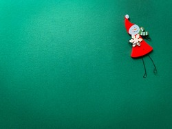 Wooden Christmas decoration toy on a green background. Winter angel with red clothes holding snowflake. Abstract minimal winter, holiday background.