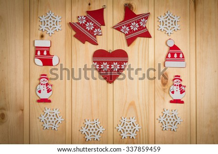 Wooden Christmas figurines snowmen snowflakes Christmas tree hat and stockings on a natural wooden background.