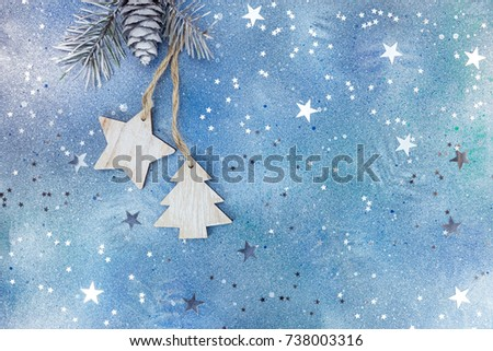 wooden christmas holiday decorations on silver-blue background with star confetti #738003316