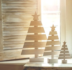 Wooden Christmas tree against window.