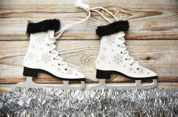 Wooden Christmas tree toy Skates with snowflakes, tied with rope, on white tinsel imitating ice. Wooden background. Creative  New Year composition.