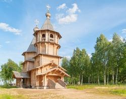 Wooden church against blue sky and birch grove background. Pavlitsevo, Arkhangelsky region, Russia.
