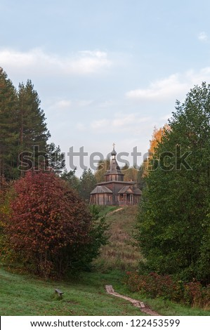 Wooden Church of the Kazan icon of the Mother of God on a hill with path among trees. Vladimirskoe village, Nizhegorodsky region, Russia.
