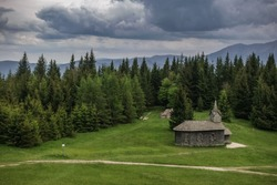 wooden church on a green meadow with many pinetrees in the mountains