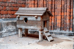 wooden city house for cats on the background of a brick stone wall