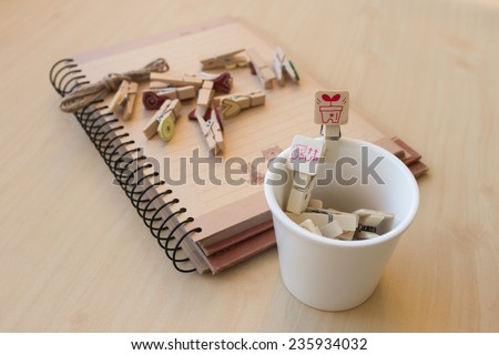 wooden clip set for paper clip in mini cup and paper clip put on notebook, concept of Romantic and in love, focus to the red wooden clip