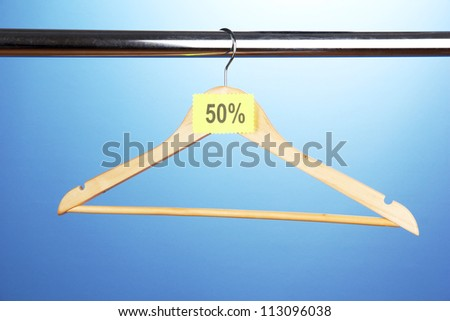 wooden clothes hanger as sale symbol on blue background