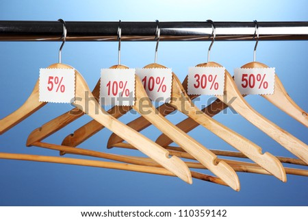 wooden clothes hangers as sale symbol on blue background