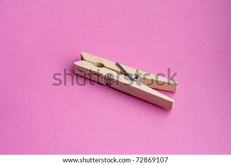 Wooden clothes peg on pink background