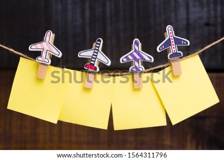 wooden clothespin with little airplanes holding empty paper notes for copy space on a wooden background ornaments decorative creative idea travel destinations