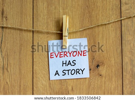 Photo of  Wooden clothespin with white sheet of paper. Text 'everyone has a story'. Beautiful wooden background. Business concept, copy space.