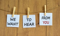 Wooden clothespins with white sheets of paper. Text 'we want to hear from you'. Beautiful wooden background. Business concept, copy space.