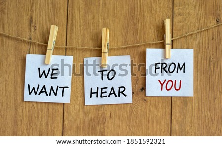 Photo of  Wooden clothespins with white sheets of paper. Text 'we want to hear from you'. Beautiful wooden background. Business concept, copy space.