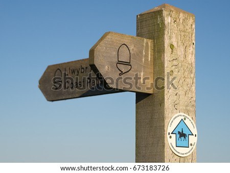 Wooden coast path sign post. Clear blue sky with copy space.