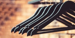 Wooden coat hanger clothes. Fashionable different types of hanger. Wood hangers coat. Many wooden black hangers on a rod. Store concept, sale, design, empty hangers.
