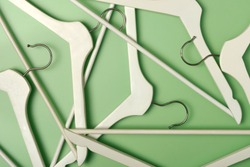 Wooden coat hanger / clothes hanger on a green background. Potential copy space above and inside hanger.