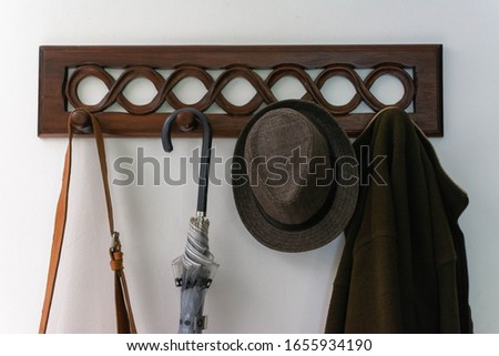 Wooden coat rack with a bag, an umbrella, a hat and a coat hanging on it, on a white wall Foto d'archivio ©