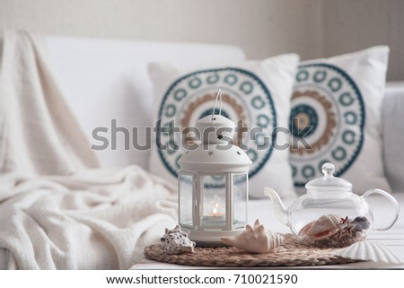 Wooden coffee table with lantern and cozy sofa with pillows. Living room interior and home decor concept. Toned image #710021590