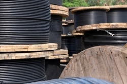 Wooden Coils Of Electrical wire Outdoor. High and low voltage cables in the storage. Large cable for electrical work