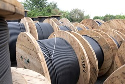 Wooden Coils Of Electrical wire Outdoor. High and low voltage cables in the storage. Large cable for electrical work.