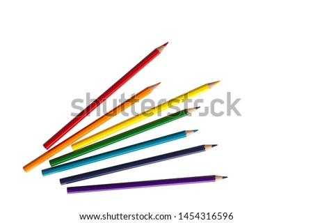 Photo of wooden color pencils arranged in bulk on a white isolated background