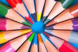 Wooden color pencils lie on a circle. The tips of the pencils look in the center of the circle. The concept of creativity