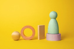 Wooden colored figures are isolated on a yellow background. Abstract background of wooden objects. Geometric composition. Scene with geometrical forms.