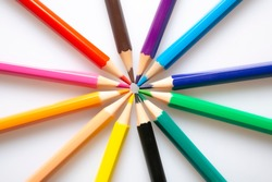 wooden colored pencils on white background arranged in circle