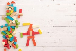 Wooden colorful bricks are scattered on a white wooden table. On the table are multicolored wooden blocks in the shape of a siren-headed monster. School, education and training concept