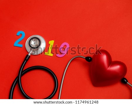 Wooden colorful on text 2019 banner for health care and Red heart love medical concept. black stethoscope,on table red background. #1174961248