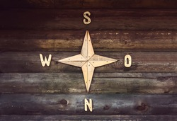 Wooden compass on a wooden wall in a country house. Decorated wall in the form of a compass, indicating the parts of the world North, South, West, East.
