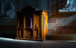 Wooden confessional in the old church in the sunlights