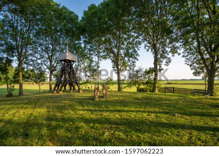 Wooden construction with a church bell in the countryside of the Dutch province of Friesland, with an old cemetery. stock photo