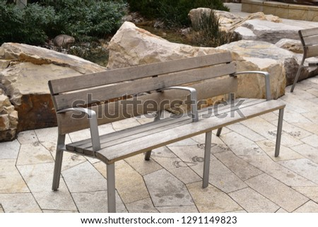 Wooden contemporary bench in contemporary modern setting outdoors #1291149823