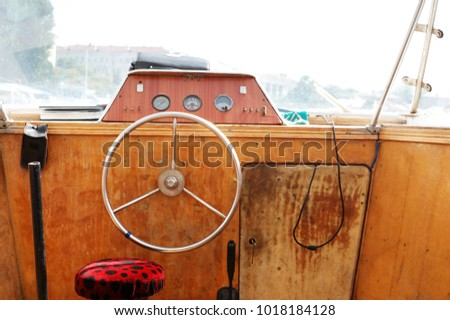Wooden control panel with metal steering wheel on the captain bridge of the old motor boat #1018184128