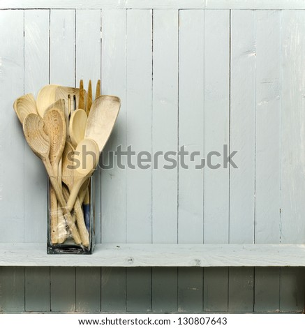 Wooden cooking utensils on shelf; good copy-space; photographed against rustic wall; add your own text to the blank spine of the 'cookery book'