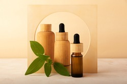 Wooden cosmetics containers in the round concrete arch with green fresh leafs.Concept of the zero waste packaging.Eco friendly cosmetic,made from the natural materials.