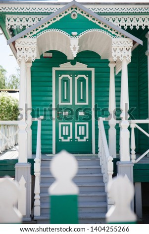 Wooden cossack house with carved wooden porch in Starocherkassk with woodcarving, green facade white carved platbands