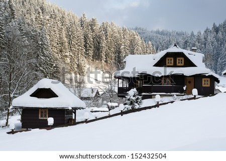Wooden cottage holiday house in mountain holiday resort covered with fresh snow in winter.
