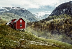 Wooden cottage in the valley. Flowers. Stone snowy mountains. Stalheim, Norway. Fog. Vintage